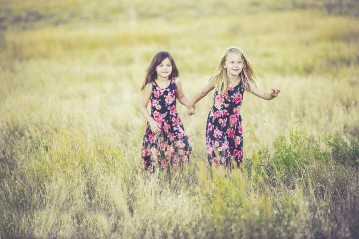 two sisters in floral dresses run through grass holding hands
