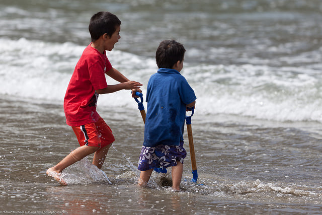 Two young brothers with blue shovels playing in the surf