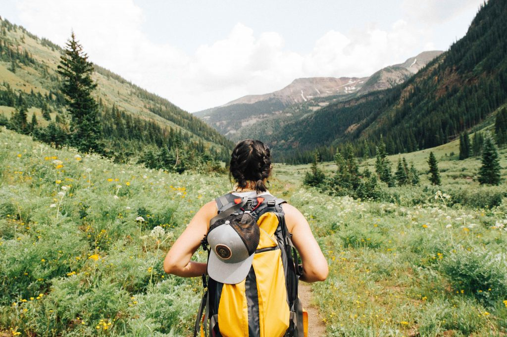 Woman with backpack hiking through a valley full of wildflowers