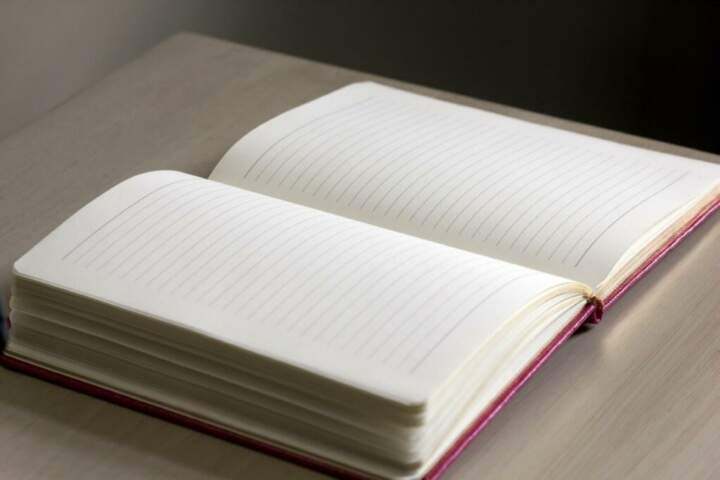 a black notebook with a red cover is open on a table
