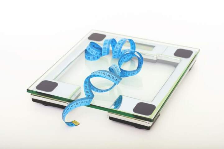 glass weigh scale and blue measuring tape on white background