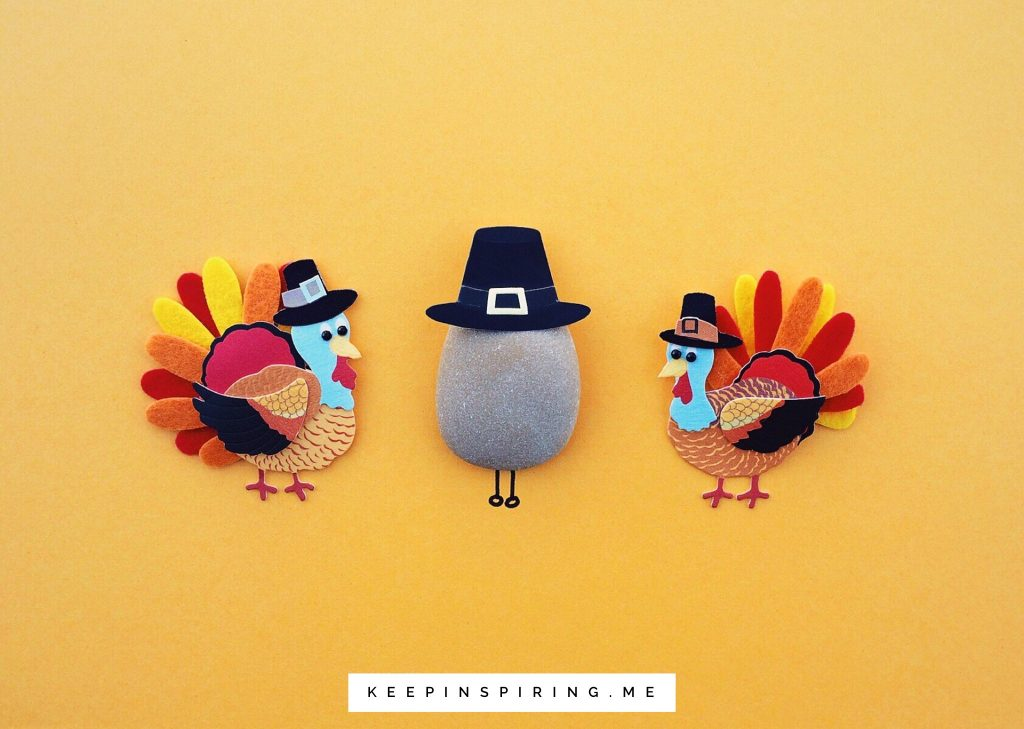 Felt cutouts of turkeys and a felt pilgrim hat atop a small stone