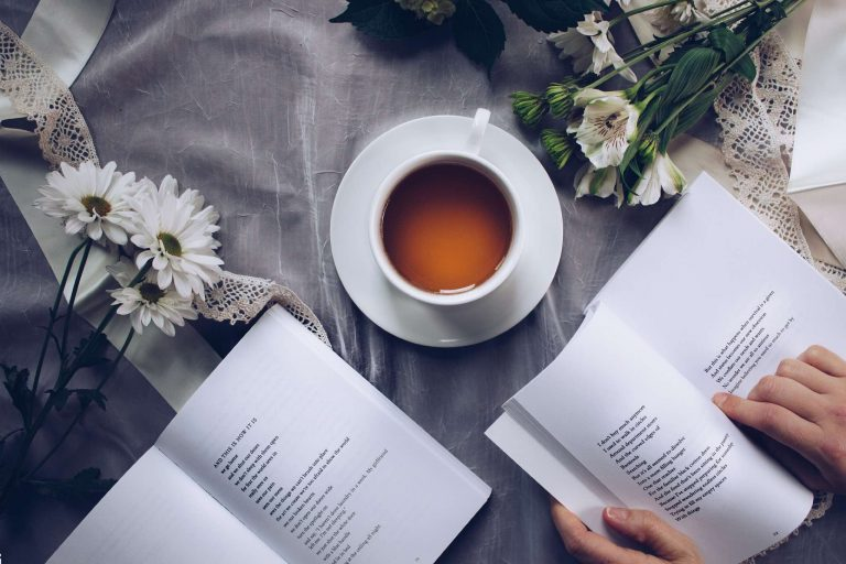 a cup of black tea on a saucer with two open books