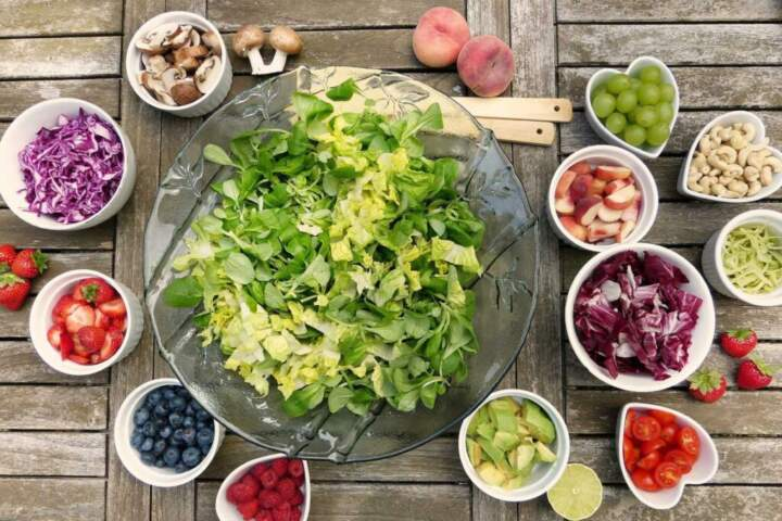 a bowl of lettuce with smaller bowls of toppings