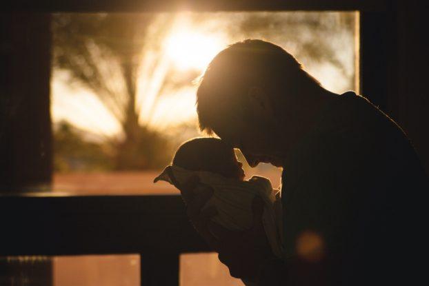 a dad cradles his newborn baby at sunrise
