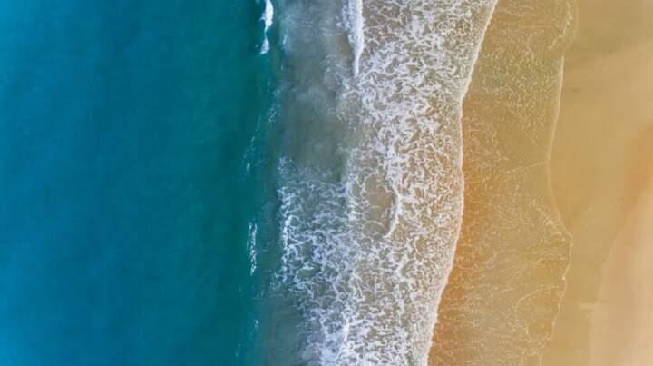 the ocean washing up on a golden sandy beach