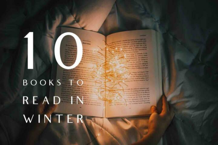 An open book lit with fairy string lights on a cold night in winter